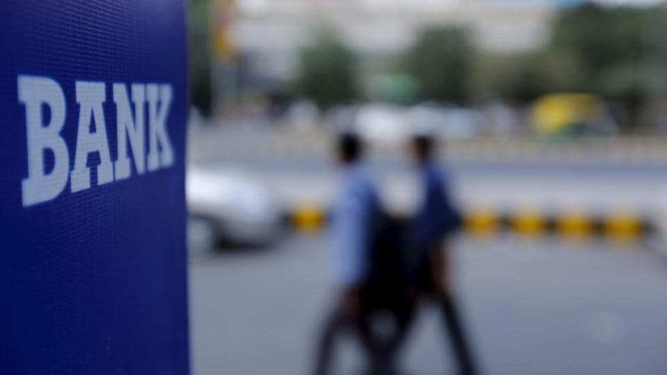 Commuters walk past a bank sign along a road in New Delhi. Services are likely to be affected on Wednesday and Thursday as the bank strike begins across India.