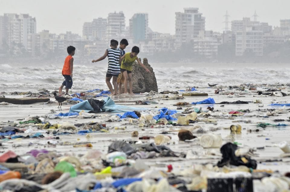 Children play amidst garbage on Juhu beach in Mumbai, on Monday, May 28.