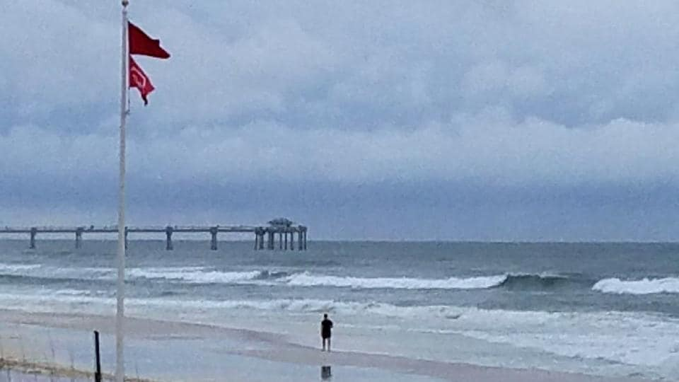 A person walks along the beach as a subtropical storm approaches Monday, May 28, 2018, in Fort Walton Beach, Florida. North Carolina's governor is urging his state's residents to exercise caution as rains from a subtropical depression spread into his and other Southern states.