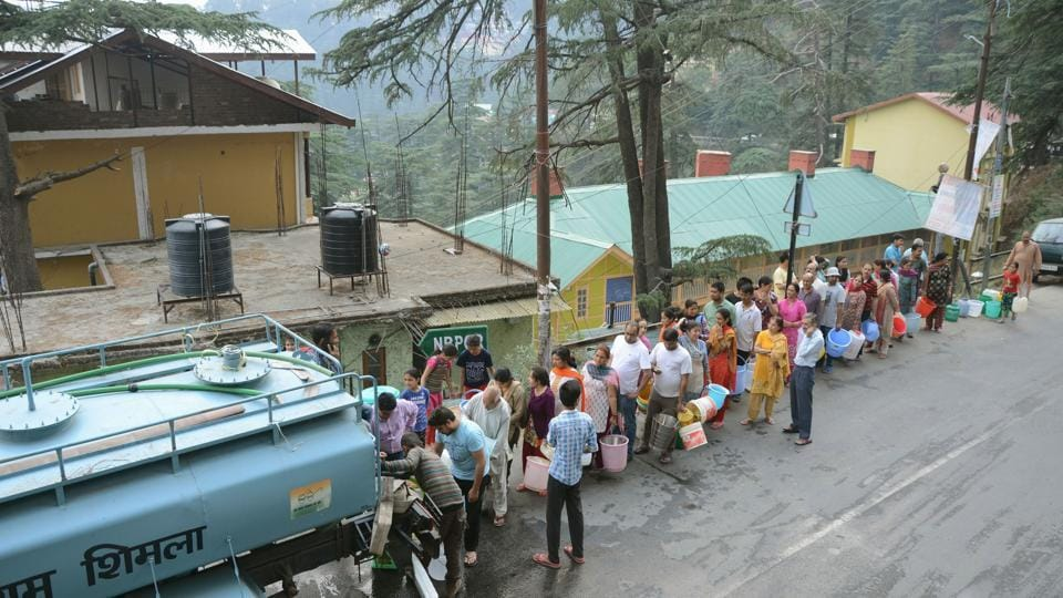 Residents queue up to collect drinking water from a tanker in Shimla.