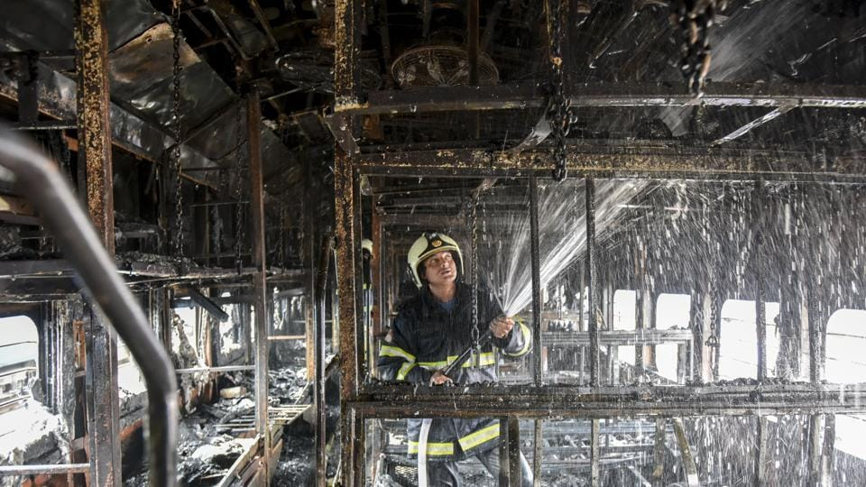 A fire-fighter douses the fire inside the coach of a train parked at Chhatrapati Shivaji Maharaj Terminus  railway yard in Mumbai on Tuesday.