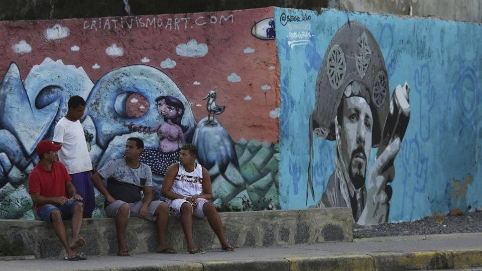 A group of men talk on a sidewalk in the Brasilia Teimosa slum that was urbanized by an initiative of Brazil's former President Luiz Inacio Lula da Silva, in Recife. A booming economy under da Silva's 2003-2010 governments, which included hikes to the minimum wage and several social welfare programs, helped many of the country's poor. (Eraldo Peres / AP)