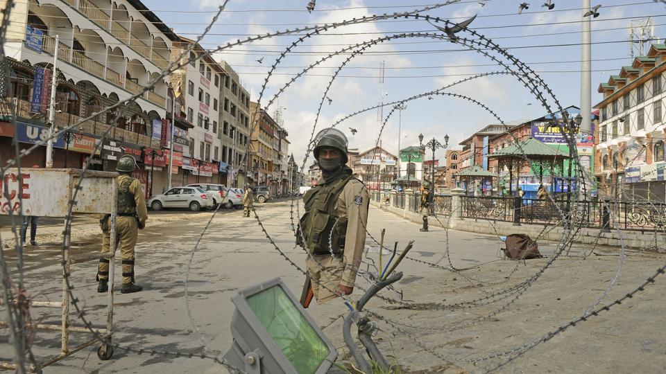 Paramilitary soldiers stand guard near a temporary barricade in Srinagar on May 19, 2018.