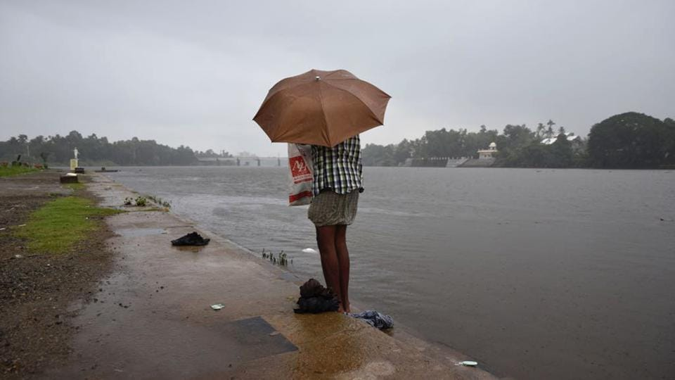 A man dresses up holding an umbrella as it started raining after he bathed in the River Periyar in Kochi, Kerala, on May 29, 2018.