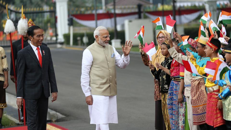 PM Narendra Modi waves at Indonesian school children waving Indonesian and Indian national flags as Indonesian President Joko Widodo looks on during the welcoming ceremony at Merdeka Palace in Jakarta, Indonesia.