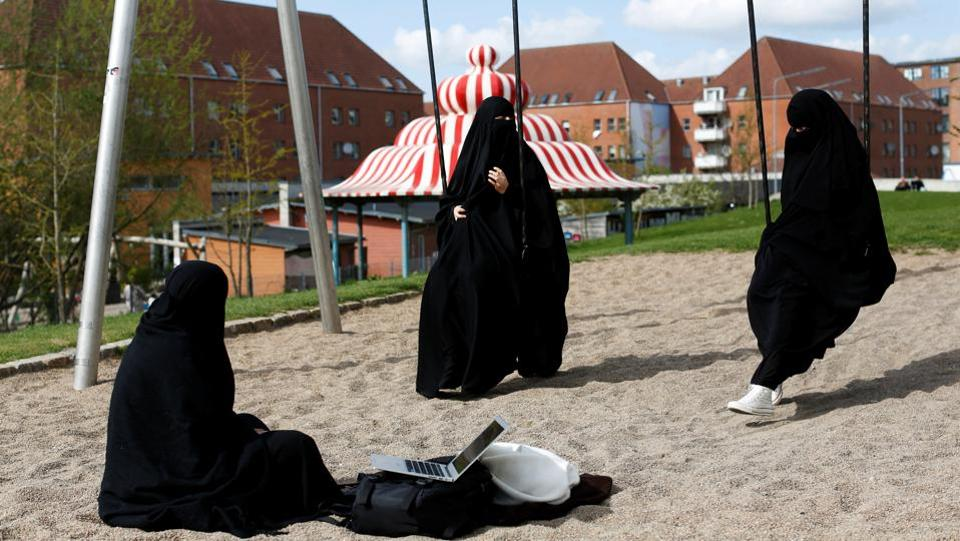 Zaynab (C) a Mjolnerparken resident, sits with her friends Amira and Sabrina in Superkilen. Some Mjolnerparken residents say the government drive could improve communities by reducing crime and boosting job prospects, but others fear it will simply entrench divisions by creating a parallel society where different rules apply. (Andrew Kelly / REUTERS)