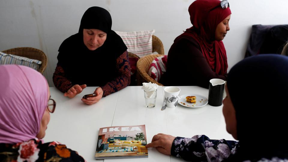 "Women look at an IKEA catalogue in Cafe Nora, a social club for women. A ghetto manifests stigma in other spheres. ""I went to a doctor when I was younger with a backache and the doctor asked me if my husband beat me, and I was like 'no!'"" narrated Umm-Meyounah, a mother-of-two who was born to Danish parents and married an immigrant from the Middle East. (Andrew Kelly / REUTERS)"