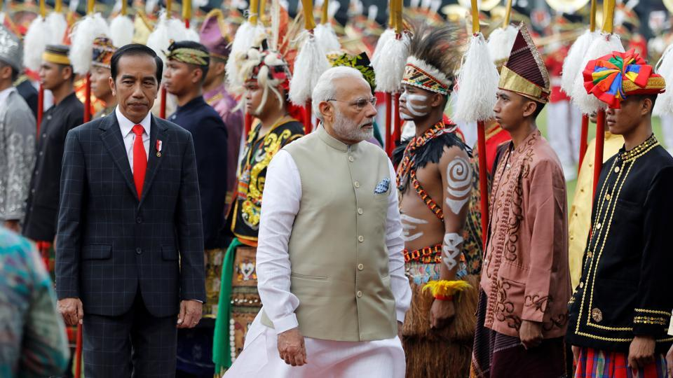 Prime Minister Narendra Modi reviews guard of honour accompanied by Indonesia President Joko Widodo at the presidential palace in Jakarta, Indonesia.