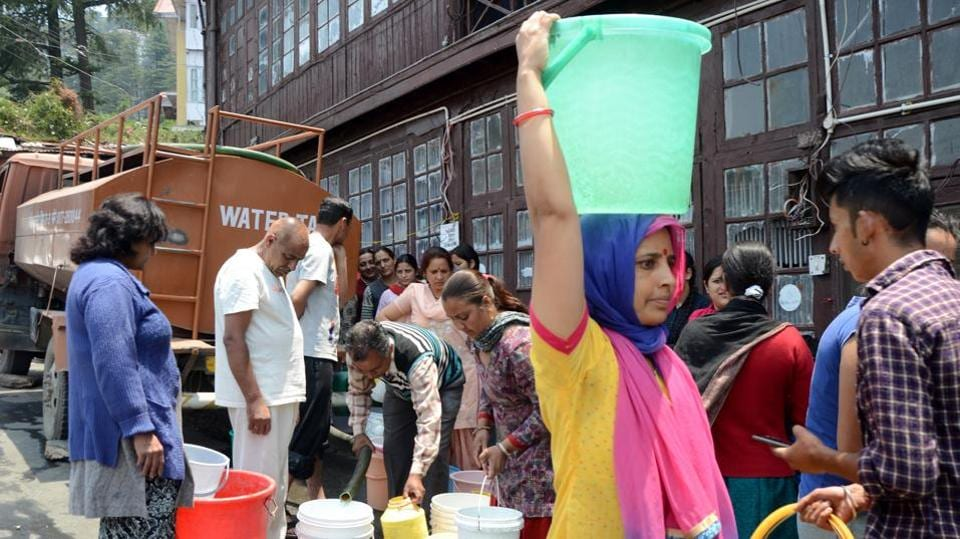People fill water from the tanker during water crisis at US Club area in Shimla city on Wednesday.