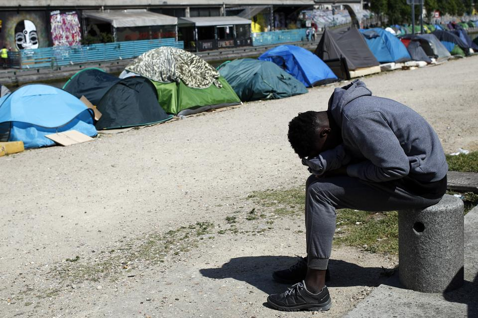 "A migrant takes a nap near tents alongside the Canal Saint-Martin in Paris. City Hall says it has spent 30 million euros since 2015 helping refugees, bolstering state aid, as well as 80 million euros each year on isolated minors. ""This is an issue of dignity,"" said Pierre Henry, head of an aid group, France Terre D'Asile. ""Street camps should not exist in our country."" (Francois Mori / AP)"