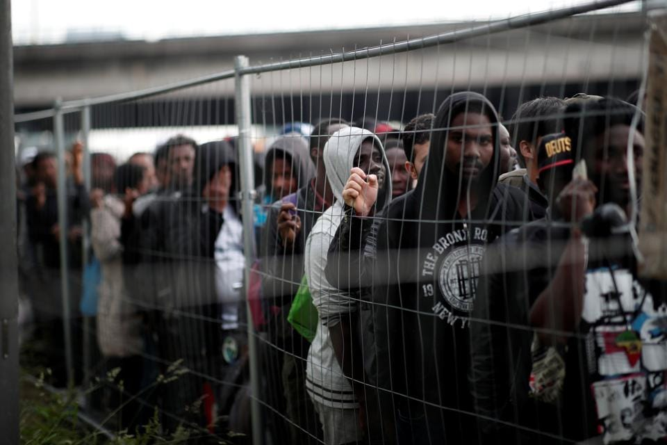 The encampment held at least 1,400 migrants, local officials have said, but 1,016 were cleared out, put in buses and taken to gymnasiums in the region. Several hundred migrants apparently fled before the evacuation. (Benoit Tessier / REUTERS)