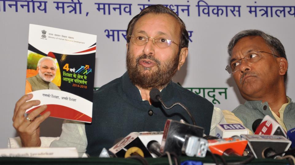 Union HRD minister Prakash Javadekar shows a brochure on works done by the Modi government in past four years, at a press conference in Dehradun on Friday.