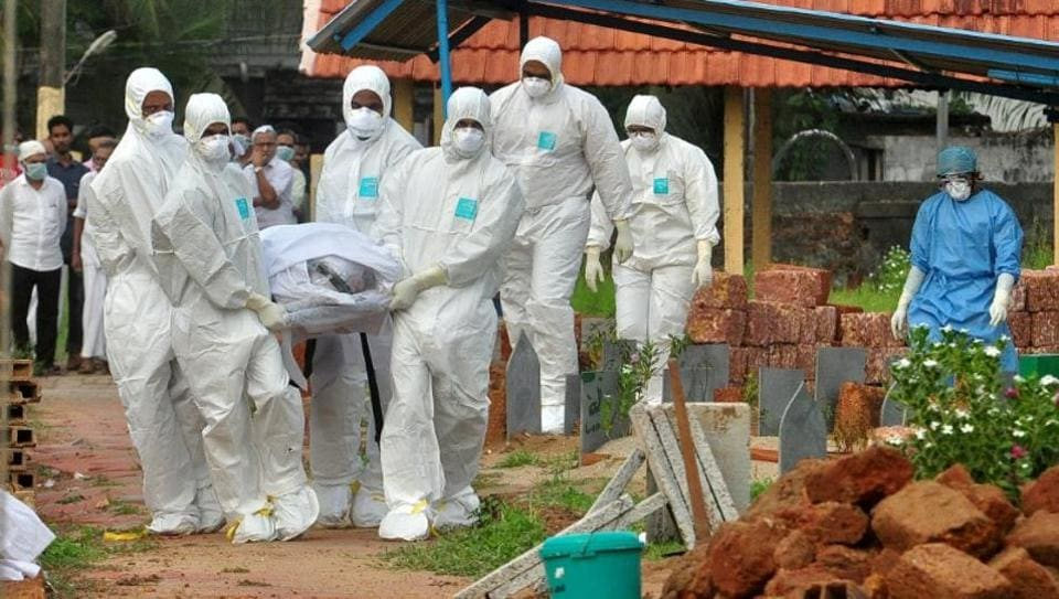 Doctors and relatives don protective gear to carry the body of a Nipah victim in Kozhikode recently.