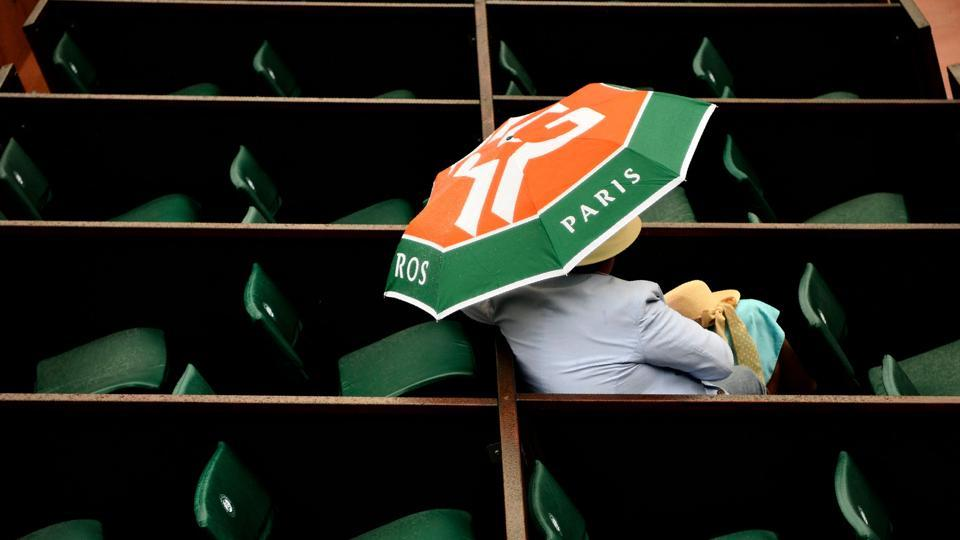A spectator shelters under an umbrella as rain falls during the men's singles first round match between Croatia's Marin Cilic and Australia's James Duckworth on day three of the Roland Garros 2018 French Open tennis tournament in Paris on May 29, 2018. (Christophe Simon / AFP)