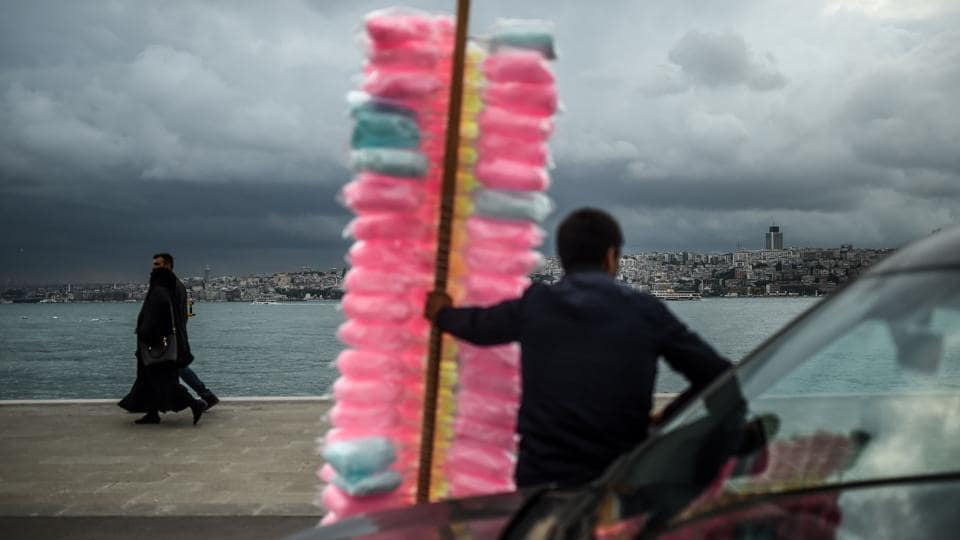A vendor sell cotton candies near Bosphorus at Uskudar district of Istanbul  during the holy month of Ramzan on May 28, 2018. (Bulent Kilic / AFP)