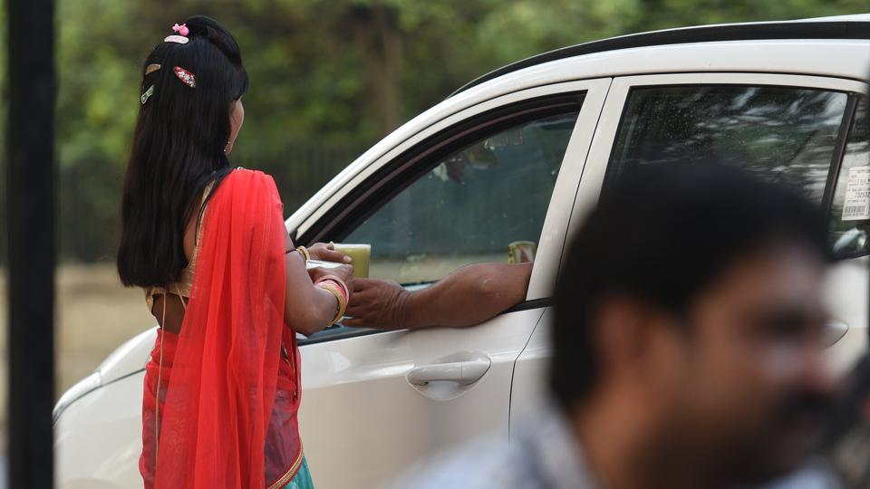 "Ramgani, a 17-year-old from Datunda, serves a glass of juice to a customer in the car. Ramgani and her sister Pinki earns around Rs.800 – 1000 per day and on being asked if they ever felt uncomfortable while working, Ramgani said, ""That it does not affect me at all, as long as I ensure each person buys no less than 7-8 glasses. And in case someone behaves indecently, I have by father and brother along to tackle them."" (Raj K Raj / HT Photo)"