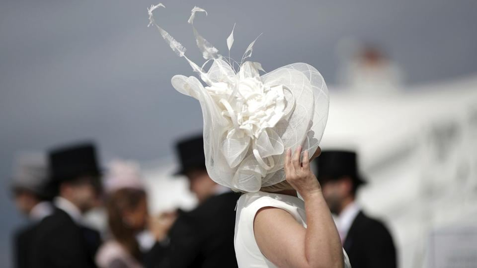 A racegoer adjusts her hat during derby day of the 2018 Investec Derby Festival, at Epsom Downs Racecourse, England. Saxon Warrior is the odds-on favourite to win the Derby.  (David Davies / PA via AP)