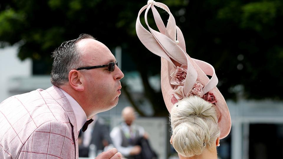 A racegoer blows at an insect perched on a woman's hairdo during Ladies Day at The Investec Derby Festival.  (REUTERS / Peter Nicholls )