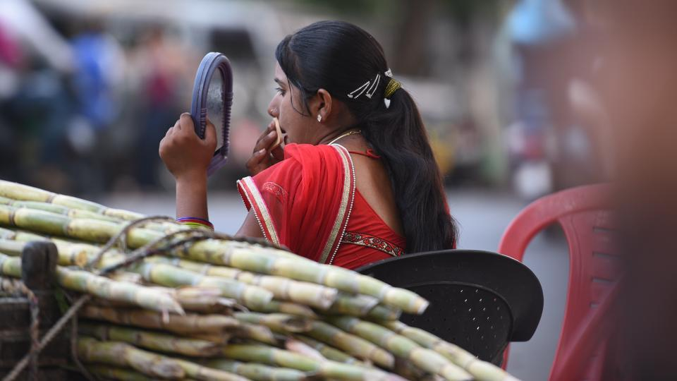 A woman vendor touches up her make-up near her sugarcane juice stall. An estimate of 800-1000 women hailing from Rajasthan's Tonk district come to Kota during the summer to run these stalls.  What is unusual is their emphasis on going the extra mile while dressing up to serve their customers. (Raj K Raj / HT Photo)