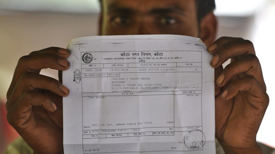Hari Ram Meena, a sugarcane juice seller displays a permit slip issued to him by the Kota Municipal Corporation. Most of these sellers are members of the Meena community, who're engaged primarily in agriculture. Permits from the municipal corporation are obtained after paying the statutory charges of Rs. 9050 levied for permission to ply their trade from the pavement located in the Nayapura, not far away from Talwandi, where Kota's famed educational institutes are situated. (Raj K Raj / HT Photo)