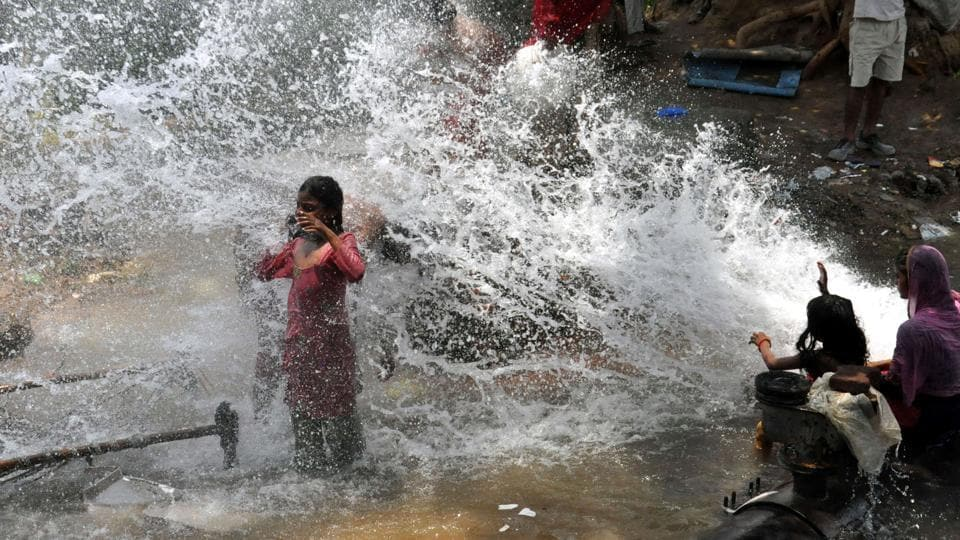 Children play in the water gushing out of a broken water supply pipeline at sector 27/42 chowk in Gurugram. Other districts of Haryana such as Hisar, Fatehabad, Jind and Panchkula have also reported a massive rain deficit. Worst hit is Hisar, which is reeling under a 83% rain deficit. (HT Photo)