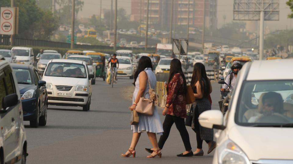 During a hot summer day, women are seen crossing the Delhi - Gurugram expressway, possibly looking for some form of public transport.   (Parveen Kumar / HT Photo)