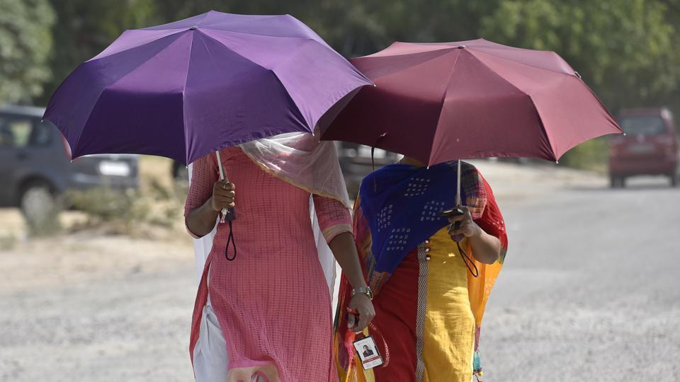 Umbrellas are out early in the city, and not to shield people from the rain, but from piercing heat that north India is facing this summer.  (Sanjeev Verma / HT Photo)