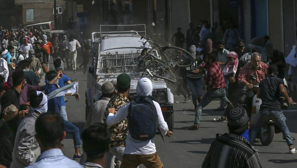 Protesters throw rocks, bricks and a cycle on a CRPF jeep in Srinagar on June 1, 2018. Two people were injured after the v   ehicle ran over them.