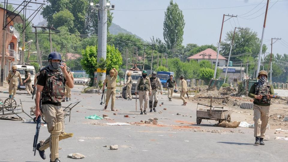 Security personnel patrol a deserted street during a curfew imposed to maintain law and order in Srinagar.