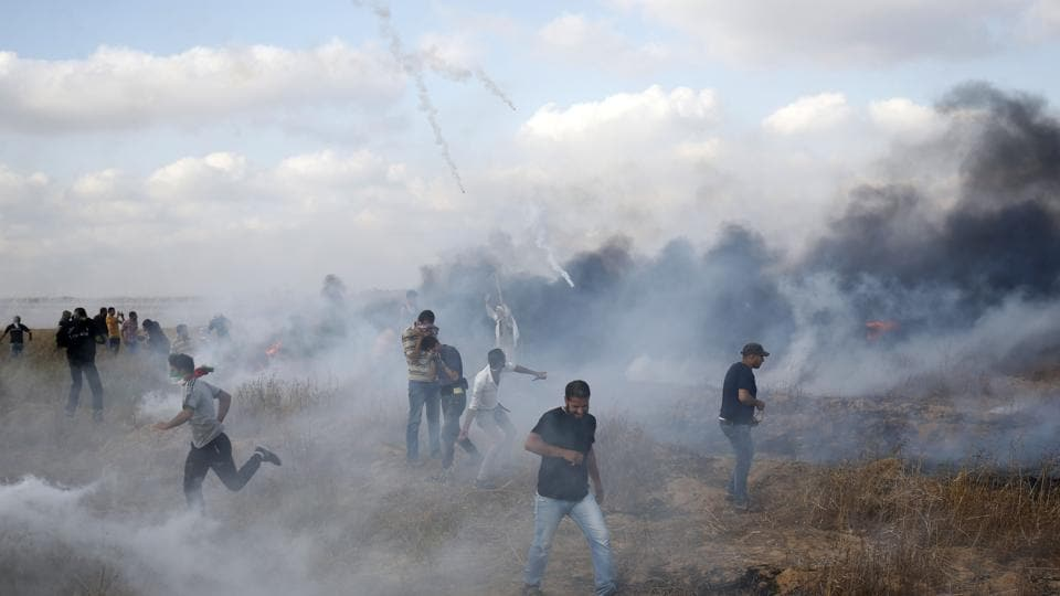 Palestinian protesters flee from incoming tear gas canisters during clashes following a demonstration along the border with Israel east of Khan Yunis in the southern Gaza strip on June 1.