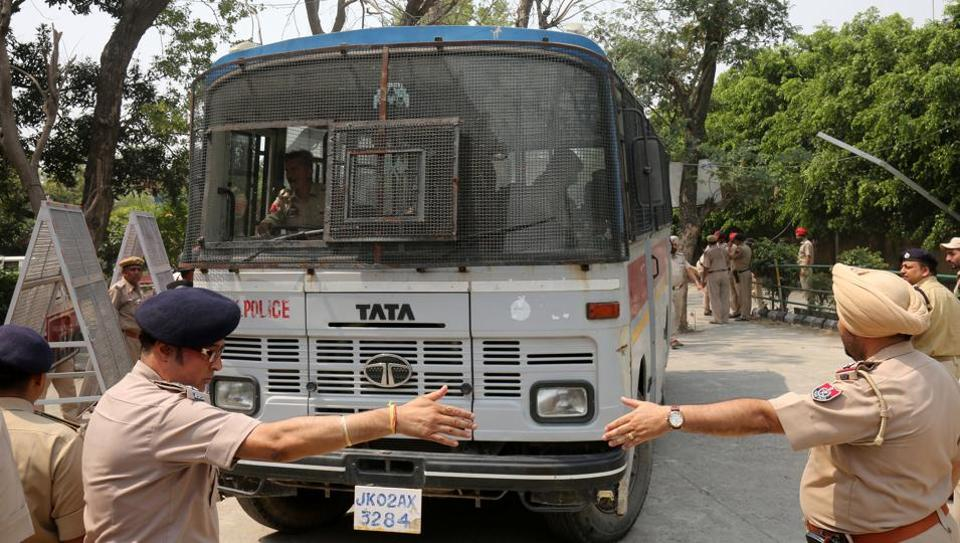 Police officers gesture as a vehicle carrying accused in the rape and murder of an eight-year-old girl in Kathua, near Jammu, enters a court premises in Pathankot, Punjab, on May 31, 2018.