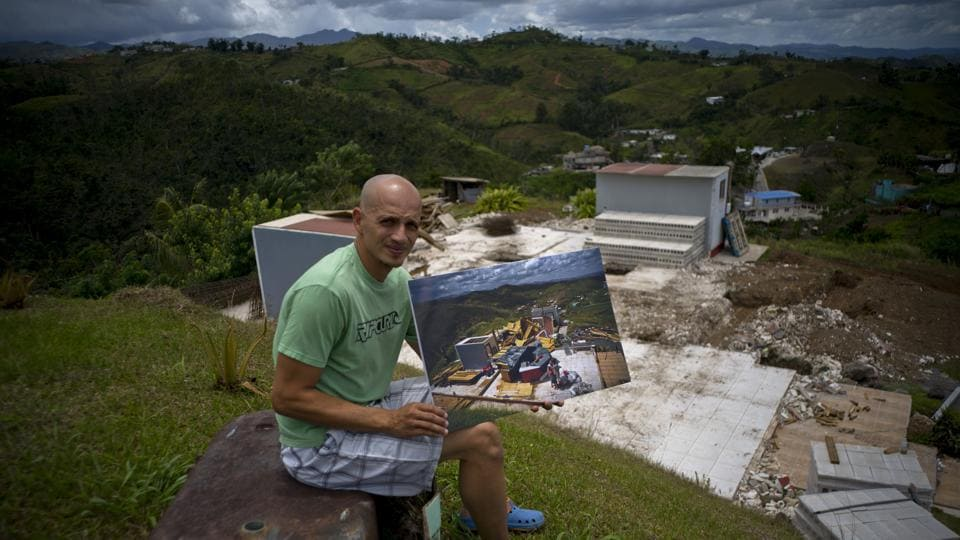 Rafael Reyes sits at his property in the San Lorenzo neighbourhood of Morovis holding a photo of him taken on October 7, 2017 amid his rubbled wooden home. The 41-year-old father and husband who collects Social Security has been living with his in-laws and said he plans to begin rebuilding work with FEMA's $31,000 assistance. Instead of wood, Reyes said this time he'll build with stones. (Ramon Espinosa / AP)