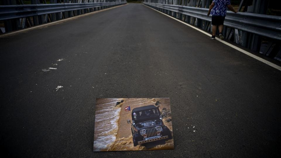 A photograph of a jeep crossing a river on October 7, 2017 is placed on the new bridge that stands where the storm washed out the old one. Because of its collapse, people on both sides were left stranded, turning a 45 minute commute to the other side into a three hour odyssey. (Ramon Espinosa / AP)