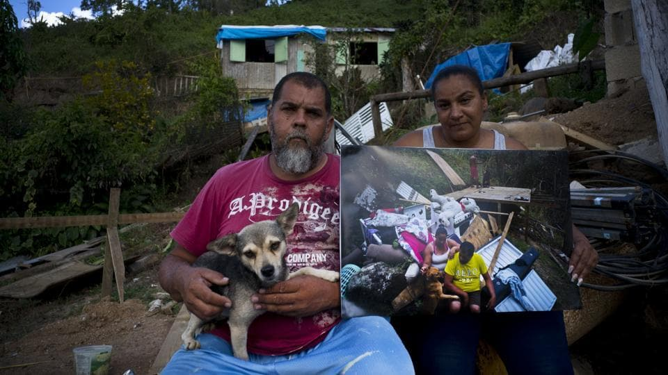 William Fontan Quintero and his wife Yadira Sostre in Morovis pose with a printed photo shot in their home destroyed by the hurricane last year. Since then, they've built a small wooden house with help from family where they live with their two children. Like many, they are still waiting for FEMA's approval to build a permanent house. (Ramon Espinosa / AP)