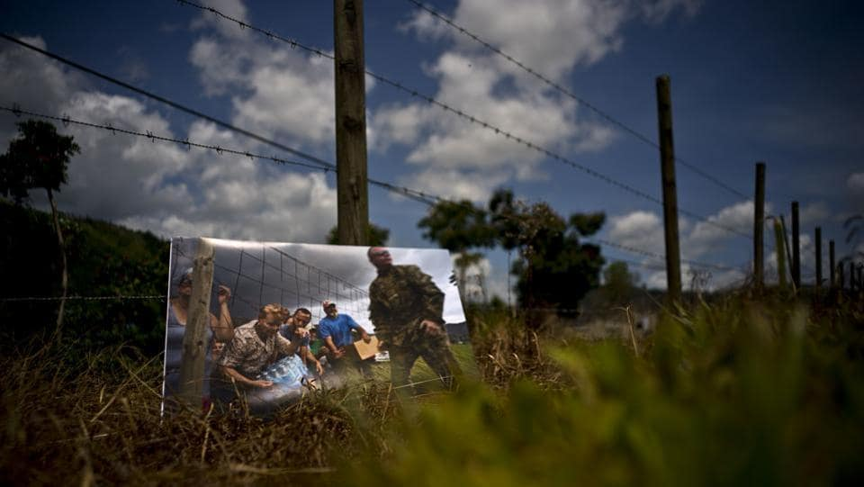 A photo print is kept at the same spot where Puerto Rican National Guards delivered food and water to desperate residents in the aftermath of Hurricane Maria on a farm in Morovis. For two months after the storm's passing, stranded residents would come to this spot for supplies handed out by the National Guard. (Ramon Espinosa / AP)