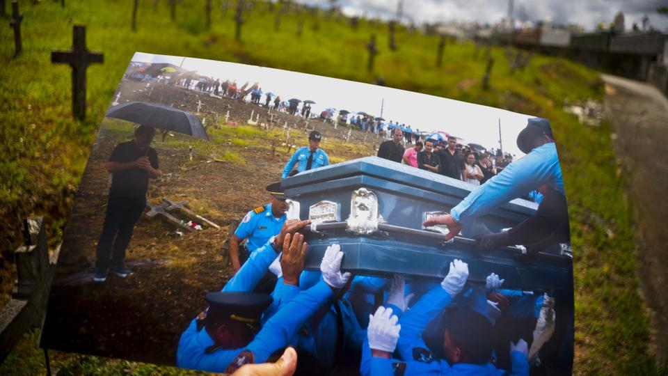 AP photographer Ramon Espinosa holds a photo taken on September 29, 2017 showing police lifting the coffin of an officer killed during the hurricane while crossing a river. Eight months since, local police still lack about a dozen officers due to resignations and retirements. Puerto Rico's bankruptcy has frozen promotions, salaries, new hires and even shut some police academies. (Ramon Espinosa / AP)