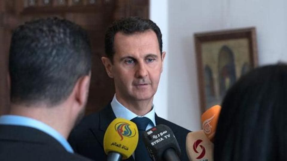 A handout picture released by the official Syrian Arab News Agency (SANA) on March 4, 2018, shows Syrian President Bashar al-Assad (C) talking to reporters in Damascus