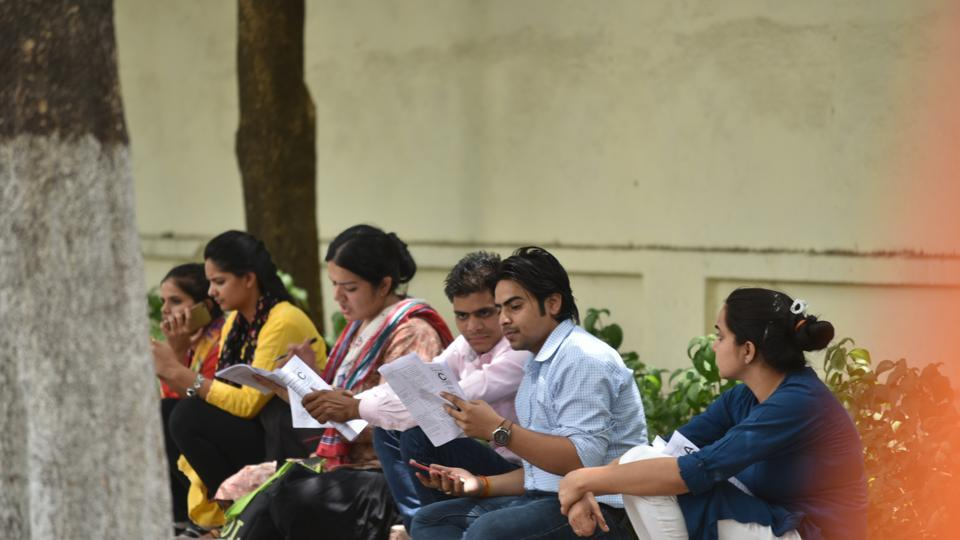Aspirants going through the general studies question paper after appearing in first paper of UPSC civil services preliminary examination at School of Excellence in Bhopal on Sunday.