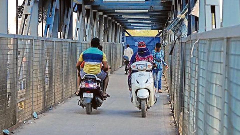 Bike riders approach from both sides on a foot overbridge leaving no space for people to walk. The Iffco Chowk FoB is accessed more by bikers than pedestrians to cross the road.