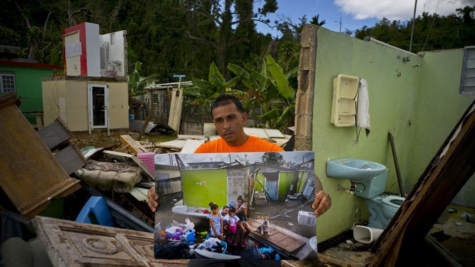 "Arden Dragoni holds a photo showing him with his family members in the remains of his destroyed home, which remains in shambles in Toa Baja, Puerto Rico. The unemployed construction worker and security guard is currently separated as his wife and his children live in a FEMA subsidized apartment. ""The hurricane brought us many calamities but my lesson was to value my family from my heart,"" Dragoni said. (Ramon Espinosa / AP)"