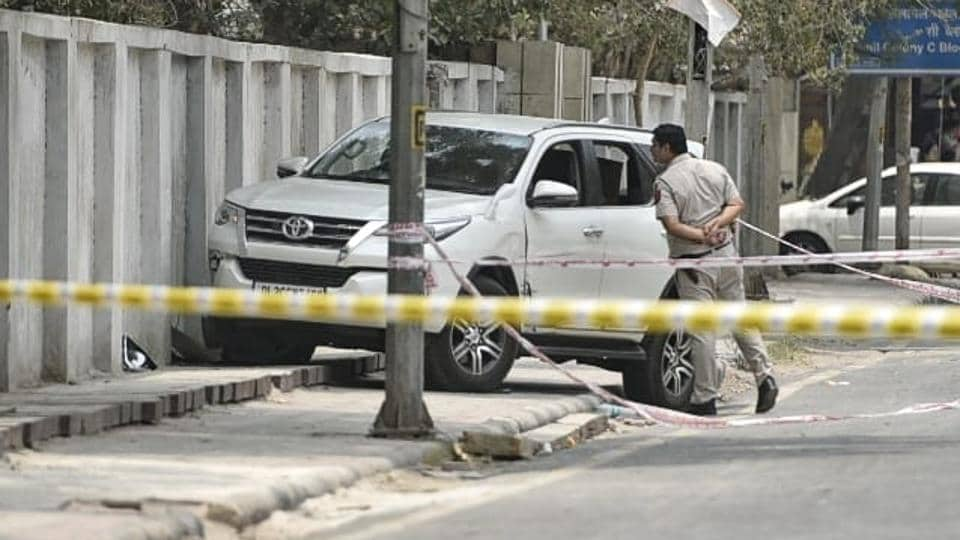 A policeman checks the stolen Fortuner SUV in which two men attempted to make a getaway after Delhi Police engaged them, at Jhilmil colony in Vivek Vihar, on Tuesday.