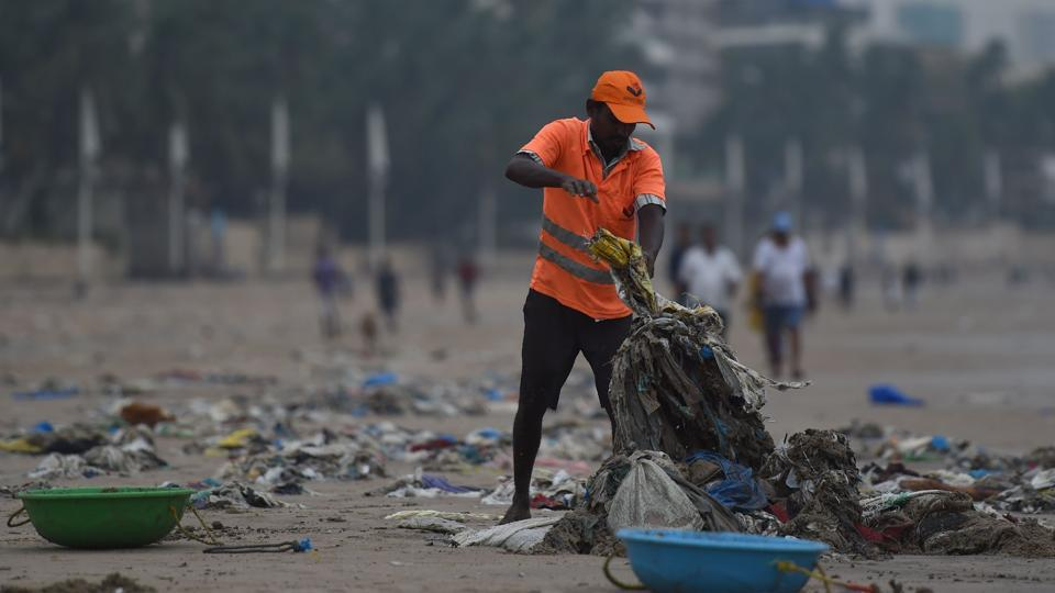 A municipal authority worker cleans up plastic waste on Juhu beach in Mumbai during World Environment Day on June 5.