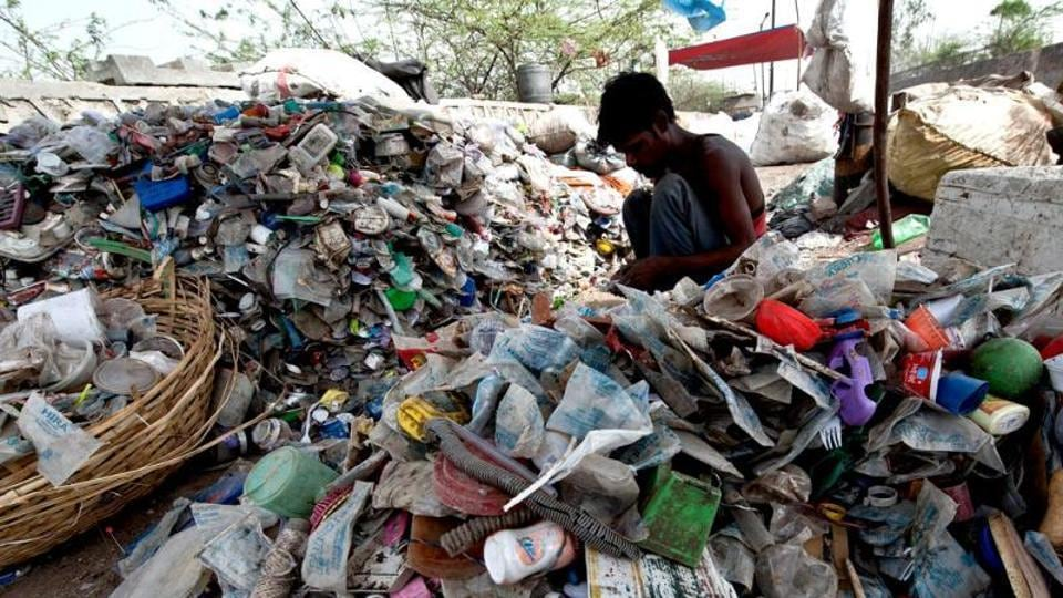 A rag-picker sorts through plastic bottles and polythene bags near a garbage land fill.
