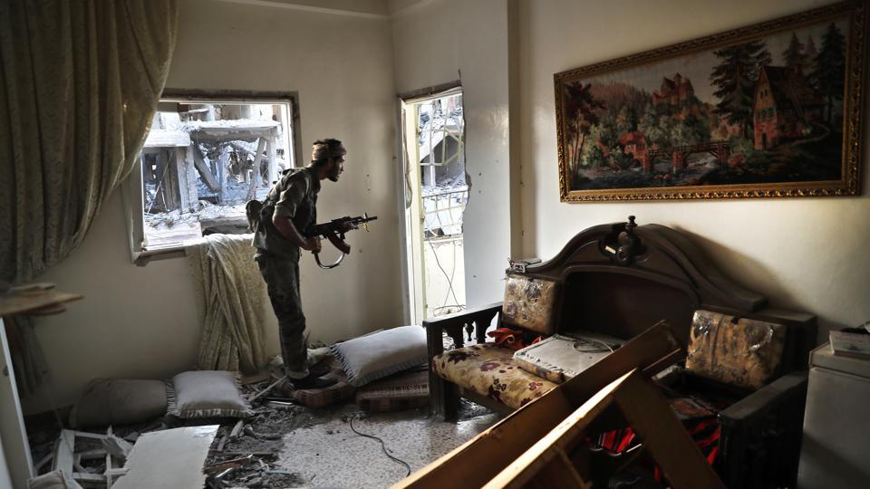 A U.S.-backed Syrian Democratic Forces fighter looks through a window from inside a destroyed apartment on the front line, in Raqqa, Syria.