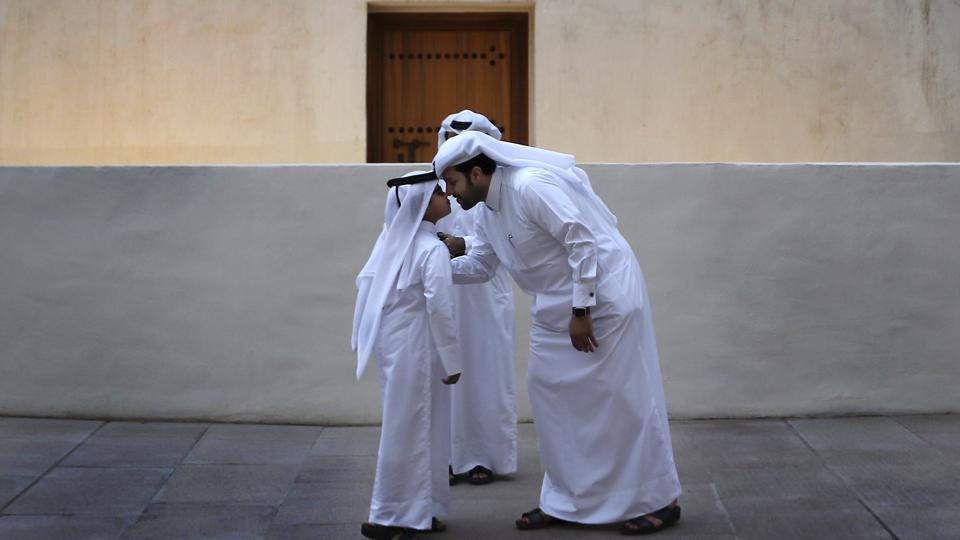 A Qatari man greets a boy in traditional Gulf Arab style in the Msheireb district of Doha. Saudi Arabia, Egypt, the United Arab Emirates and Bahrain severed diplomatic ties and transport links to Qatar last year over its alleged support of terrorist groups and warm relations with Iran. But natural gas reserves and close allies in the region have allowed Qatar to weather the crisis. (Kamran Jebreili / AP)