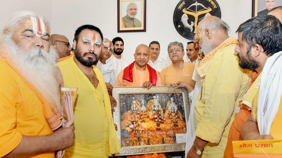 UP chief minister Yogi Adityanath poses with a delegation of sadhus and saints during a meeting over early construction of Ram Temple at Ayodhya. Taking note of alleged irregularities in wheat purchase and distribution of food grains, Uttar Pradesh Chief Minister Yogi Adityanath on Thursday suspended the district magistrates of Fatehpur and Gonda. (PTI)