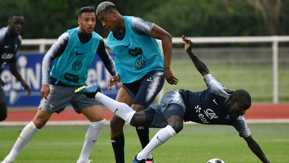 French defender Presnel Kimpembe (C) and French midfielder N'Golo Kante (R) vie for the ball in training.  (AFP)