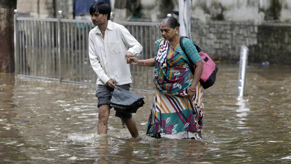 A man helps an elderly woman past a waterlogged street in Mumbai. Several parts of  the city were flooded after moderate rainfall on Thursday. Parts of central Mumbai, Elphinstone Road, Parel, Dadar TT Circle and Dadar's Hindmata had 1.5 feet of water. (Rajnish Kakade / AP)