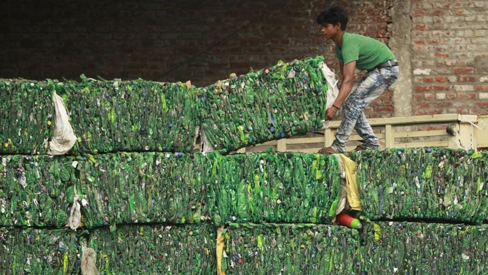 A worker loads bundles of plastic bottles onto a truck for recycling at an industrial area on the outskirts of Jammu, on June 5, 2018. (Channi Anand / AP)