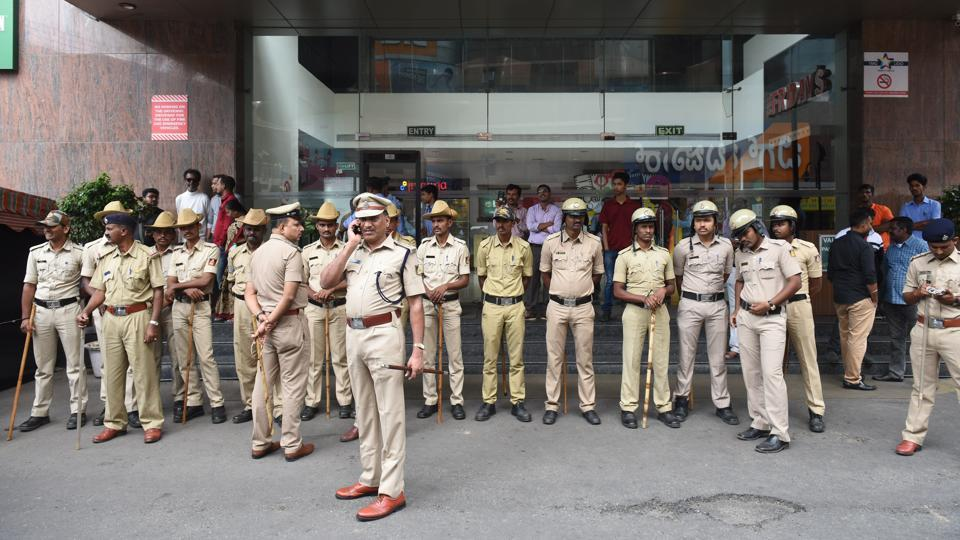 Police stands guard outside Lido Mall in Bengaluru. Widespread protests by pro-Kannada activists marred the screening of the Rajinikanth-starrer 'Kaala' in most parts of the state on Thursday. Agitators were seen requesting the 67-year-old actor's fans not to watch the movie for the sake of their Kannada brethren fighting for Cauvery water. (Arijit Sen / HT Photo)